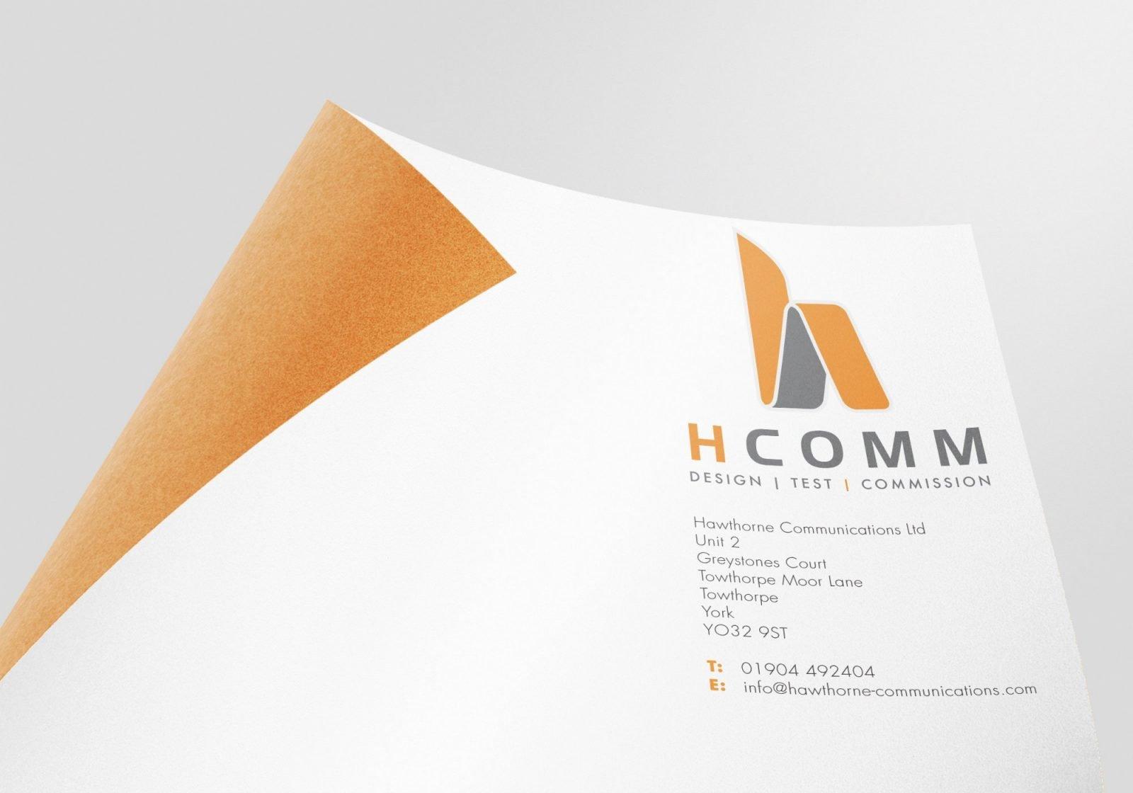 A logo close up on paper showing Hcomm Rail's logo design