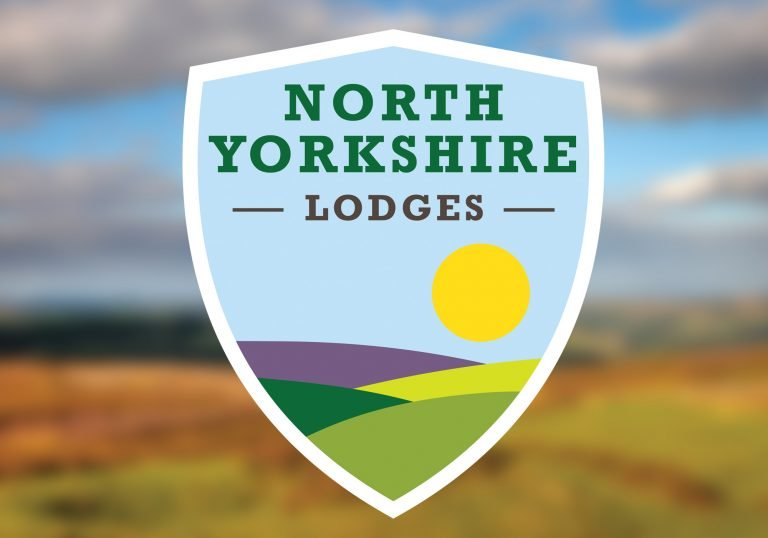 Logo for North Yorkshire Lodges on a blurry background